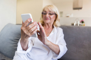 Beautiful senior woman in eyeglasses using a smartphone and smiling while sitting on couch at home