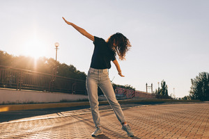 Beautiful slender girl with curly hair dancing in the city at sunset