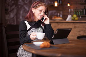 Beautiful smiling adult businesswoman while talking on the phone in front of tablet. Holding a cup of coffe in vintage restaurant