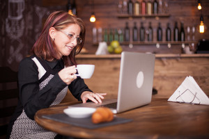 Beautiful smiling adult woman enjoying coffe while working on her notebook. Drinking coffe in vintage coffee shop
