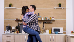 Beautiful smiling woman jumps in her husband arms at the kitchen.