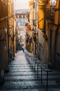 Beautiful Staircase in Lisbon. Hanging laundry in typical narrow street. Sunset in the old downtown of Lisbon, cityscape of Lissabon
