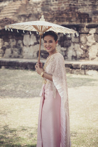 beautiful thai woman wearing old thai tradition clothes style holding bamboo wood umbrella with toothy smiling face