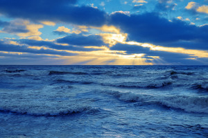 Beautiful twilight time. Sunset over sea with dramatic cloudy sky. Beautiful wild nature. Stormy weather. Trendy blue color.