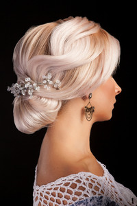 Beautiful weeding hairstyle with blonde woman isolated on blackbackground. Elegance style. Female coiffure.