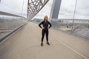 Beautiful Woman Athlete Standing At Modern Bridge In City