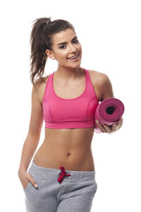 Beautiful woman holding pink exercise mat