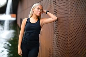 Beautiful Woman in Sportswear Leaning On Metallic Wall After Workout