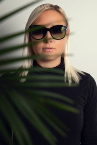 Beautiful woman with sunglasses hiding behind tropical palm leaves