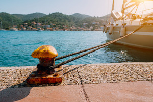 Beautiful yacht tied on the pier. Summertime feeling sunbeams, morning sunlight. Vacation on greek islands