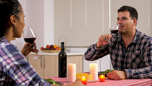 Beautiful young couple enjoying some red wine while their are having a romantic dinner. Strong feelings.