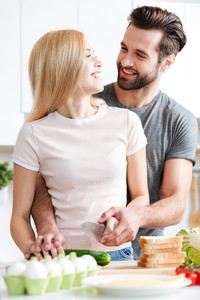 Beautiful young couple preparing healthy salad together and looking at each other at home