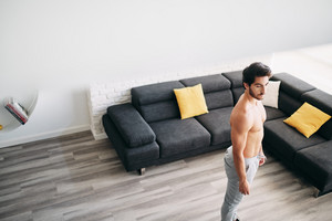 Beautiful young man training and working out at home. Handsome hispanic male athlete exercising for wellness and weight loss in his living room, taking a rest between exercises.