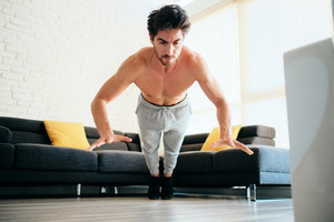 Beautiful young man training and working out. Handsome hispanic male athlete exercising with a chest routine for wellness in his living room. Latino people doing explosive pushups and sport at home.