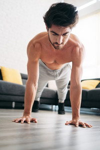 Beautiful young man training and working out. Handsome hispanic male athlete exercising with a chest routine for wellness in his living room. Latino people doing pushups and sport at home.