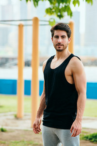 Beautiful young man training and working out in park. Handsome hispanic athlete standing and looking at camera after fitness routine. Portrait of Latino people doing Calisthenics exercise on a bar.