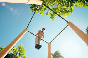 Beautiful young man training and working out in park. Handsome hispanic male athlete exercising with a chest and triceps routine for wellness. Latino people doing Calisthenics exercise and sport on a