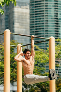Beautiful young man training and working out in park. Handsome hispanic male athlete exercising with an abdomen routine for wellness. Latino people doing Calisthenics exercise and sport on a bar.