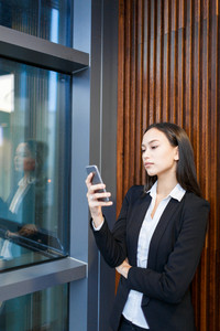 Beautiful young manager leaning to wall of office lobby and texting with her friend on smartphone, portrait shot