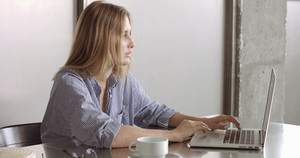 Beautiful young professional reading something on her laptop, close up