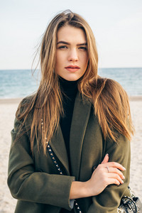 Beautiful young woman in a green coat on the beach, vertical cropping