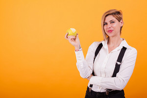 Beautiful young woman looking at the camera and holding a bitten green apple over yellow background. Fresh fruit . Casual clothes. Dental care.