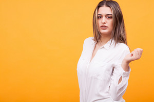 Beautiful young woman posing to the camera on yellow background. Facial expression
