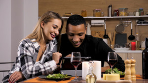 Beautiful young woman showing something on her tablet to her boyfriend while having a romantic dinner. Attractive couple