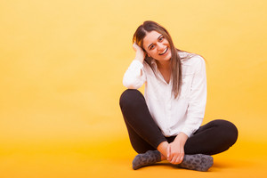 Beautiful young woman sitting down and smiling over yellow background. Cheerful girl