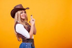 Beautiful young woman wearing cowboy costume over yellow background. Silly moment