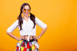 Beautiful young woman wearing funky costume over yellow background. Silly mood