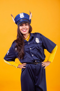 Beautiful young woman wearing Police costume over yellow background. Having fun.