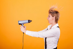 Beautiful young woman with blonde short hair using hairdryer over yellow background. . Hair care. Funny coiffure.