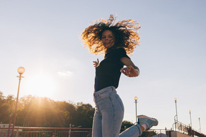 Beautiful young woman with curly hair happily jumping in city at sunset