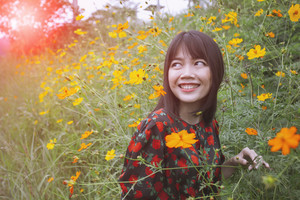 beautiful younger asian woman toothy smiling face with happiness emotion standing in yellow cosmost flower field