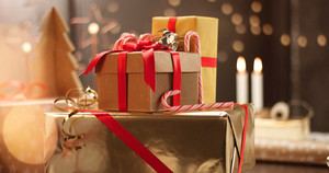 Beautifully wrapped Christmas presents on the background of stylish decorations and lights in warm golden and red tones