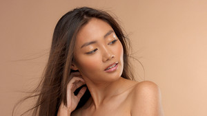 beauty asian model with blowing hair on beige background. Natural looking model