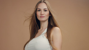 beauty woman model in studio on beige background with wind in hair bllowing it. white top