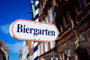 Beer garden sign. Opened shield in german biergarten on a sunny holiday. Old traditional buildung and blue sky in background. Happy day in south germany