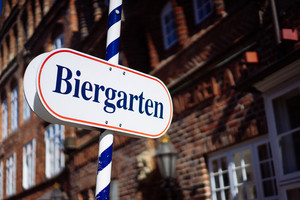 Beer garden sign. Opened shield in german biergarten on a sunny holiday. Old traditional german buildung in background. Happy day in south germany