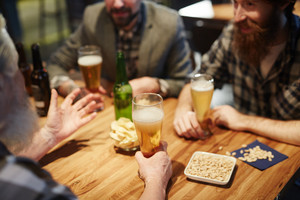 Beer in glasses and group of talking men gathered in pub