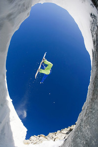 Below view of fearless sportsman jumping high over snow covered mountains on snowboard