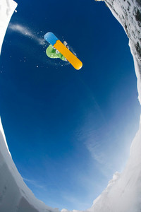 Below view of sportsman enjoying snowboarding on background of blue sky