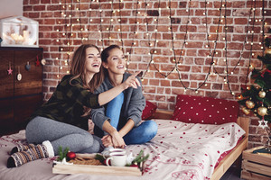 Besties spending christmas day together in bedroom