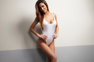 beuaty spanish woman wears white swimsuit in 80-th style in studio shoot