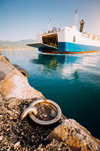 Big ferry boat with passengers and cars arrives beautiful Greek island. Summer vacation