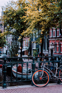 Bike parked on a bridge in Amsterdam, Netherlands. Typical cityscape