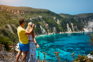 Birthday gift. Young man closing hes girlfriend eyes in front of gorgeous seascape panorama of blue lagoon. Couple love. Turquoise Petani beach on Kefalonia island Greece