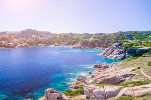 Bizarre granite rock and azure bay with sun flares in Capo Testa, Sardinia, Italy