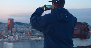 black african american treveler makes a city panorama photos on smartphone evening time